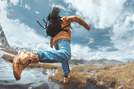 Wandelaar springt over water in de bergen. Wandelconcept met man Stockfoto