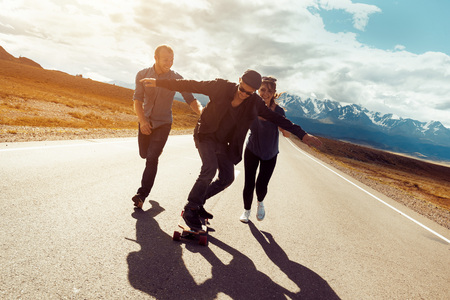 Happy friends are havin fun and skating or longboarding at long straight road