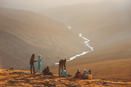 Big group of friends peoples relax on mountain top and looks at sunset