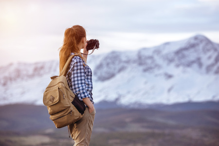 Beautiful woman with backpack is taking photo of mountain