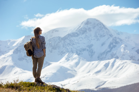 Woman with backpack stands on viewpoint and looks at mountains