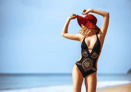 Beautiful lady stands in hat and dark swimsuit on tropical beach and smiling