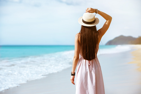 Slim beautiful lady walks is dress and hat at sea beach