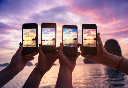Closeup photo of four hands with mobile phones taking photo of beautiful sunset over sea bay Banco de Imagens