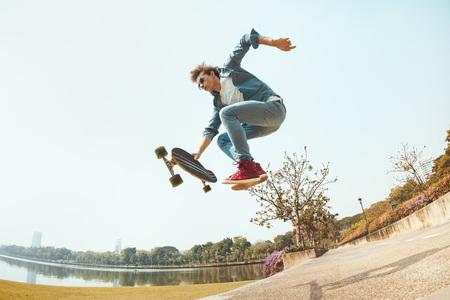 Hipster hombre salta con patineta en el parque