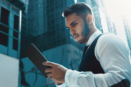 Businessman stands with tablet computer in city and read something