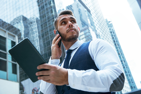 Businessman with tablet computer speaks by phone in big city