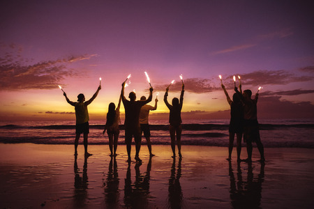 Big group of friends is having fun with sparkle lights at sea beach at sunset time
