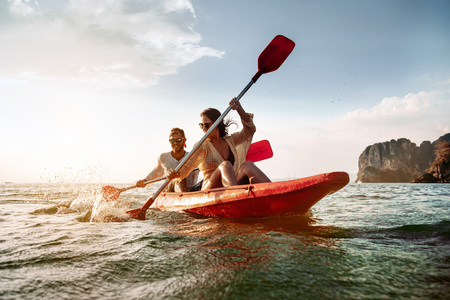 Happy couple walks by sea kayak or canoe at tropical bay