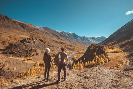 Two hikers stands on big rock and looks at mountains, river and valley