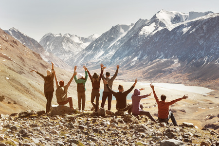 Big happy active company of friends sits in mountains and having fun with raised arms Banco de Imagens