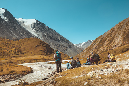 Big group of hikers having rest against mountains and river. Space for text Banco de Imagens