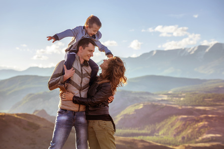 Happy family with young son stands against mountains