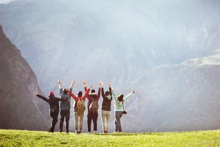 Happy hikers or friends stands against mountain valley with raised arms and having fun. Space for text