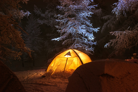 Night winter camp with group of tents in snow capped forest