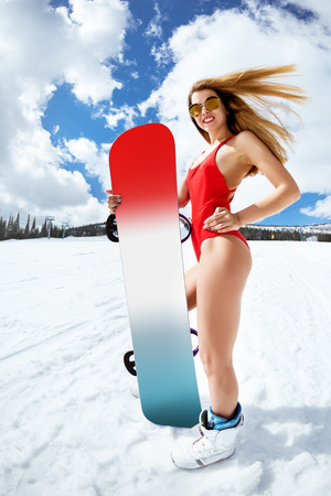 Beautiful girl stands at ski slope in red swimsuit and keeps snowboard Banco de Imagens