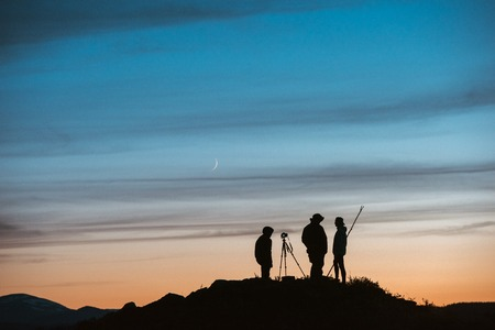 Group of silhouettes of photographers against sunset sky