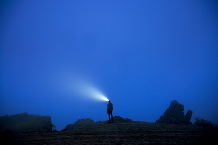Small silhouette of man with headlamp stands in foggy dusk