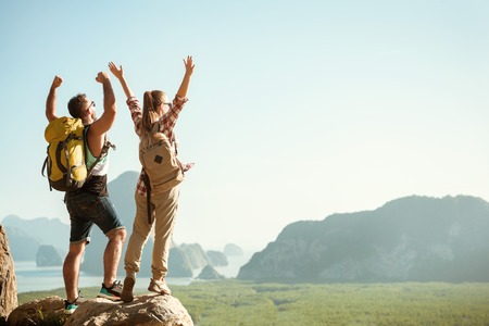 Two happy tourists stands with raised arms on viewpoint