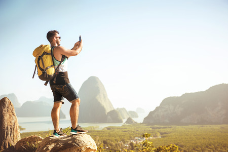 Backpacker tourist stands on big rock and takes mobile photo at viewpoint Фото со стока