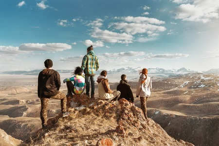Group of tourists or friends stands at viewpoint and looks at mountains