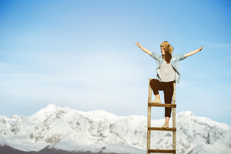 Happy girl stands on wooden staircase with raised arms against snowy mountains