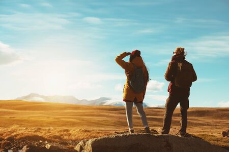 Two backpackers or travelers stands on big rock and looks at mountains