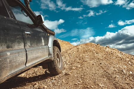 4x4 off road ready car is driving uphill. Close Up photo of wheels Фото со стока