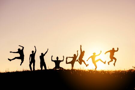 Silhouettes of big group of happy friends jumps and having fun against sunset sky Фото со стока