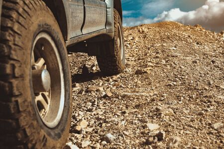 Closeup photo of all-terrain car wheels in mountains area. Off-road 4x4 car