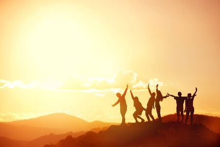 Big group of happy friends or big family silhouettes stands and having fun at sunset mountains. Space for text Фото со стока