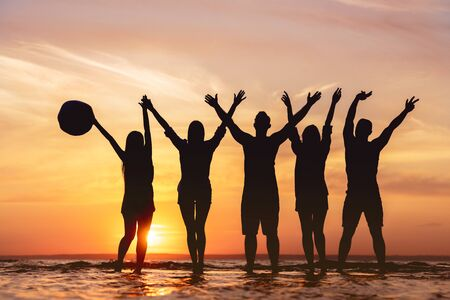 Five happy friends with raised hands having fun at sunset beach. Photo of silhouettes Фото со стока
