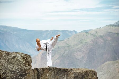 Karate athlete is standing on mountains cliff and demonstrating kicks against valley view Imagens - 131675726