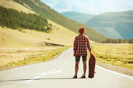 Hipster with longboard or skate stands on long straight road in mountains Stock fotó