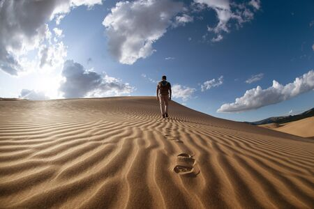 One lonely man walks in desert on dunes