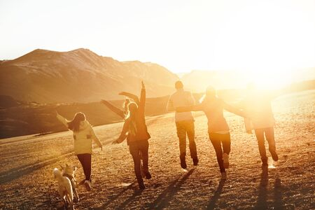 Group of happy friends or travellers is having fun in sunset light. Travel together concept Stock fotó