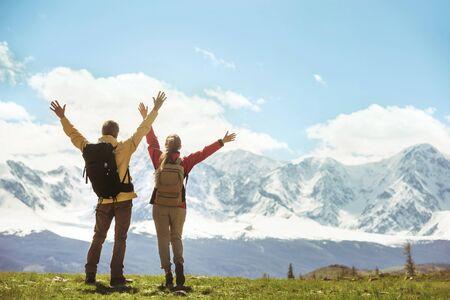 Twee succesvolle wandelaars staan met opgeheven handen tegen witte bergen