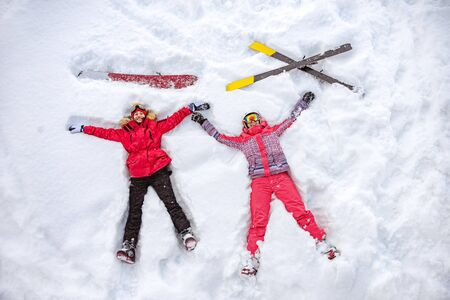 Skier and snowboarder are lying on snow with ski and snowboard and having fun. Aerial photo