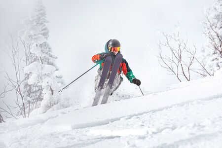 Professional skier freerides in snowy forest. Off-piste backcountry skiing
