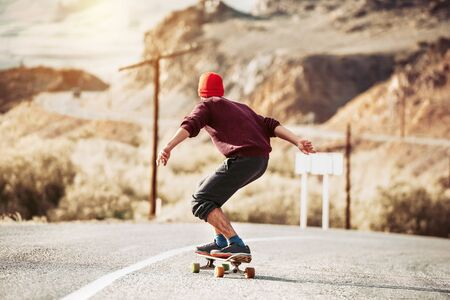 Hipster rides by mountain road on longboard or skateboard