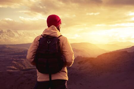 Hiker or traveler stands with backpack against mountains and looks at epic sunset sky and sun. Travel concept Stock fotó