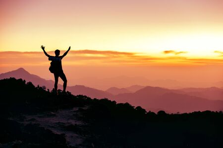 Hikers or travelers silhouette stands on mountain top against sunset with raised arms