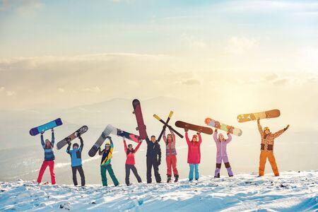 Große Gruppe glücklicher Freunde Skifahrer und Snowboarder, die Spaß haben und Ski und Snowboards auf dem Berggipfel halten Standard-Bild