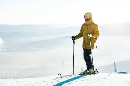 Skier stands with ski on mountain top at start of the slope Imagens - 131676001