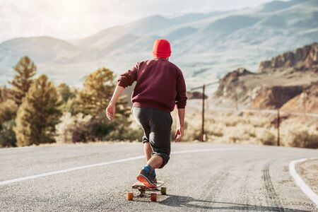 Man hipster is skateboarding at mountain road in sunset light