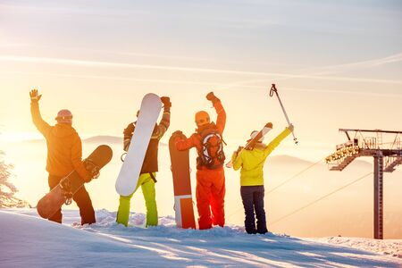 Group of happy friends skiers and snowboarders stands at sunset mountain top and having fun Imagens