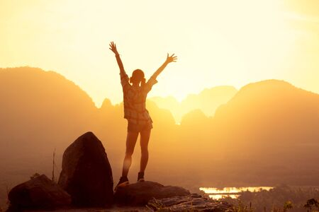 Happy slim girl stands with raised arms against sunrise or sunset, sea and islands. Phang Nga province, Thailand Imagens - 131677579