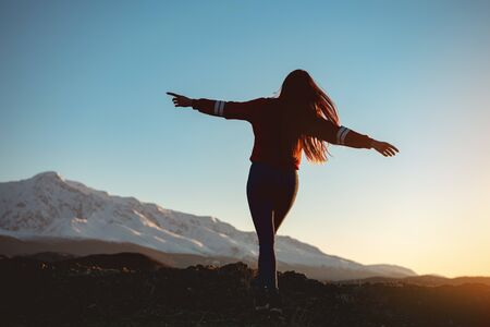 Beautiful slim girl walks with raised arms against sunset mountains and sky Stock fotó