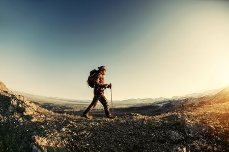 Hiker walks with backpack and trekking poles in sunset mountains Stock fotó