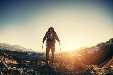 Hiker with backpack and walking poles stands against mountains